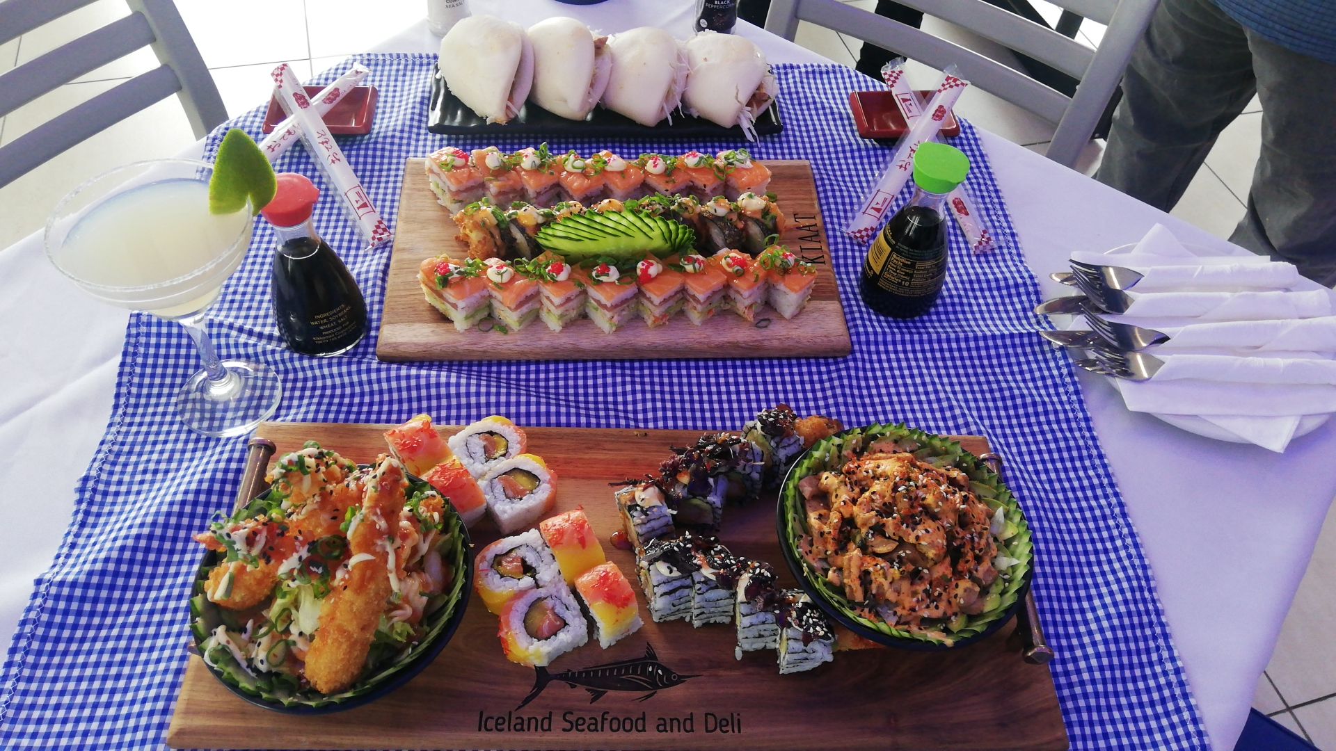 Sunninghill square | Johannesburg, Sandton, Mall, Shopping Centre, Convenient, Near Me, South African, Local, Affordable, Quality Iceland Seafood , blue and white tablecloth sushi rolls ,cutlery wrapped, sushi platter, soy sauce ,margarita , white table chopsticks