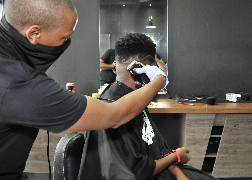 Sunninghill Square | The Classic Barber Shop, hair being styled, grey walls, African man cutting hair