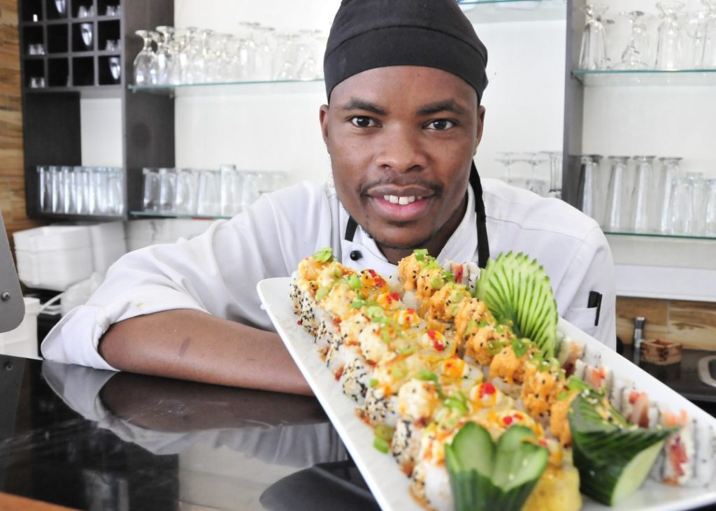 Sunninghill square   Johannesburg, Sandton, Mall, Shopping Centre, Convenient, Near Me, South African, Local, Affordable, Quality Master Sushi at the square, African chef holding sushi plate